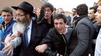 People cry before the funeral convoy carrying the coffins leaves the Ozar Hatorah school after a funeral, 20 March