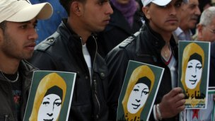 Palestinian protesters hold pictures of Hana Shalabi during a sit-in outside the Red Cross offices in Ramallah on February 28
