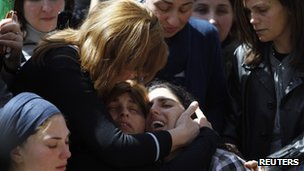 The mother of seven-year-old Miriam Monsonego (bottom right) mourns during the joint funeral service in Jerusalem for her daughter and the other three victims - 21 March 2012