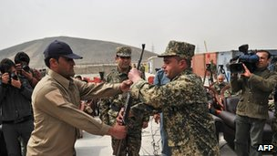 Security guard hands over a weapon to a  member of  Afghanistan's Public Protection Force