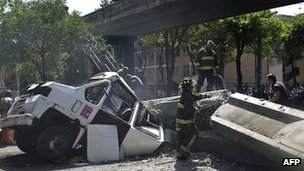 Firefighters work to remove a bus damaged by a bridge which collapsed following a strong earthquake that hit Mexico on 20 March 2012