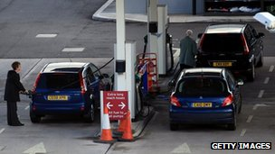 Motorists fill up their cars with petrol and diesel at a supermarket filling station in the UK, March 2012