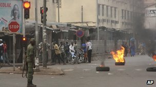 A soldier participating in a mutiny stands near civilians and burning tires lit in support of the mutiny, in Bamako, Mali on 21 March