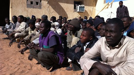 A large group of migrants sitting in rows on the ground