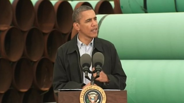 President Obama speaks in front of a stack of pipes in Cushing, Oklahoma.