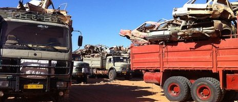 Old trucks loaded with smashed up cars