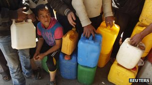 Children wait with their containers at a petrol station in Khan Younis, 22 March 2012.