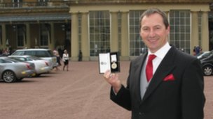 Mike Curtis with his medal outside Buckingham Palace
