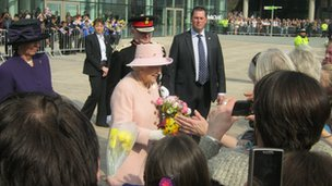 The Queen accepts gifts from the excited crowd at MediaCityUK, Salford