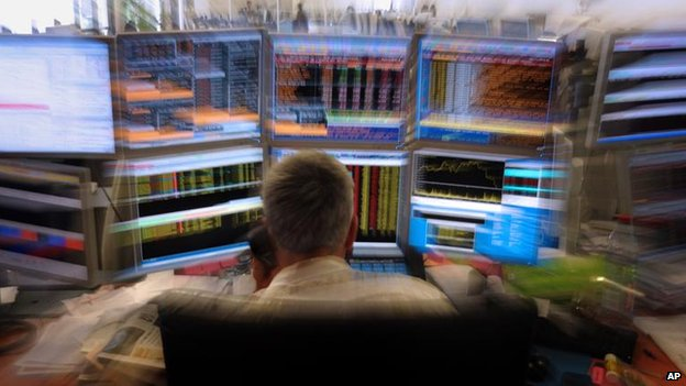 A trader watches screens in his office in an investment house