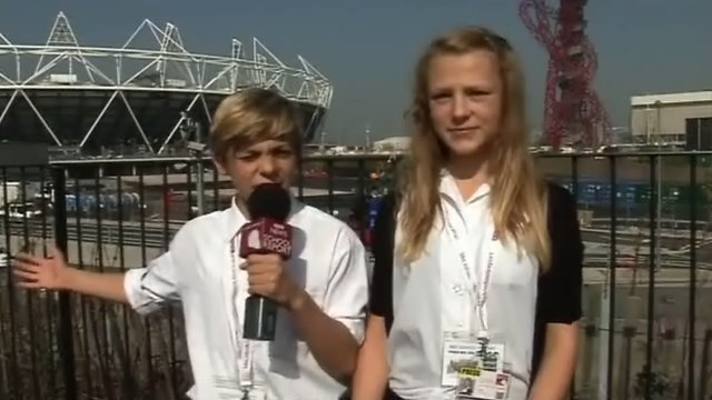 Two students stand at the Olympic park and report to the camera