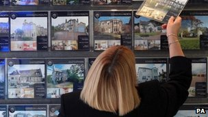 A woman looking at properties in an estate agent
