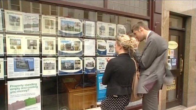First time-buyers look at properties in the estate agent window.