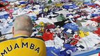 A supporter looks at tributes to Fabrice Muamba outside the Reebok Stadium