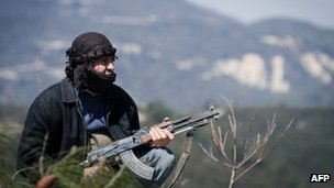 A Syrian opposition fighter crouches in hills near Idlib, 24 March