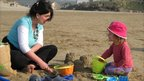 Chris Jadav, from Truro, and two-year-old daughter Lucy make sand castles at Perranporth beach, in Cornwall