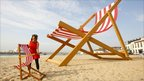 A giant deck chair sits on a beach in Bournemouth
