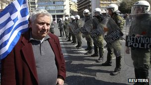 A man stands in front of a police formation during a military parade marking Greece&#039;s Independence Day in Athens 