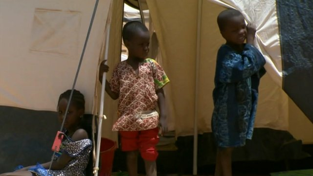 Child refugees, who have fled Mali to Niger with their family, stand outside a tent.