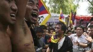Tibetan activists tend to man who set himself alight (out of picture at bottom) in Delhi - 26 March 2012