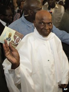 President Abdoulaye Wade holds up the ballot papers for himself and opponent Macky Sall