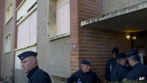 French police officers stand next to Mohamed Merah's apartment building, in Toulouse, Friday March 23, 2012