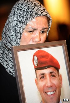French paratrooper Imad Ben Ziaten's mother Latifa carries a portrait of her son at Rabat airport, Morocco, 24 March
