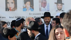 Photos of victims look down from a wall of the Ozar Hatorah Jewish school in Toulouse as mourners gather, 25 March
