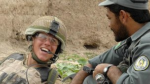 A Guardsman of the 1st Battalion the Coldstream Guards shares a joke with a member of the Afghan National Police