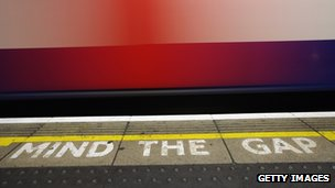 Tube train passes Mind the Gap sign