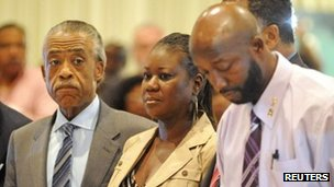 The parents of Trayvon Martin stand with Reverend Al Sharpton at a rally marking one month since their son's death in Sanford, Florida, 26 March 2012