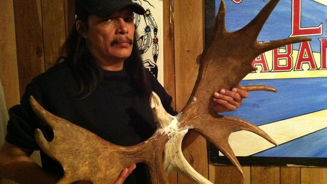 Man holding eagle carved out of moose antlers