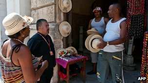 Pilgrims buy handicrafts before attending a mass at the Catedral of Havana on 27 March 2012