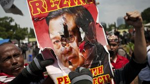 Protesters tear the poster of the Indonesian President