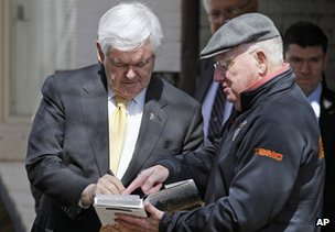 Newt Gingrich (left) autographs his book in Annapolis, Maryland, on 27 March 2012