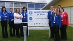 Whitecross School pose in front of their school sign