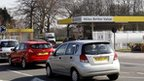 Cars queuing outside petrol station
