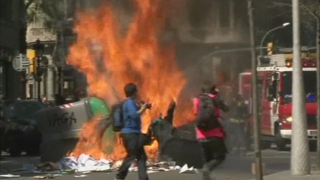 Garbage on fire in the street, with upturned bin and people standing in front.