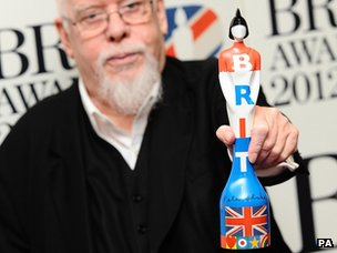 Sir Peter Blake holding this year's Brit award which he designed