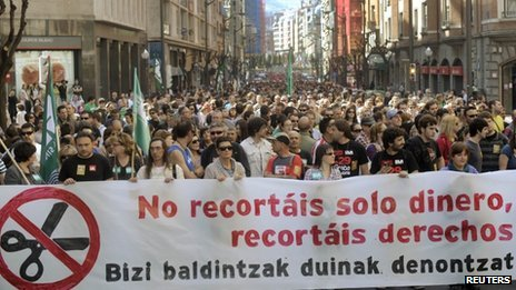 "Protesters in Bilbao carry a banner reading ""You are not just cutting our money, you are cutting our rights"", 29 March 2012"