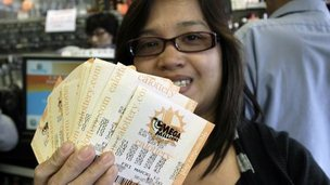 A woman holds her lottery tickets in Lawndale, California 29 March 2012