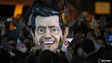 A large figure of Enrique Pena Nieto's head surrounded by crowds at a rally