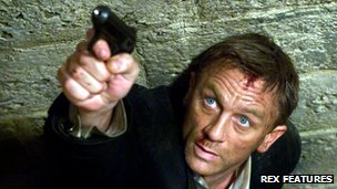 Daniel Craig aiming a gun in character as the fictional spy James Bond