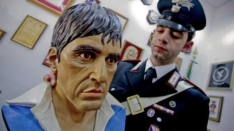 A police officer with the full-sized bust of Al Pacino as Tony Montana