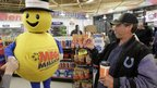 A customer receives a free lottery ticket from a Hoosier Lottery mascot in Zionsville, Indiana 30 March 2012