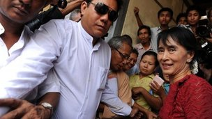 Myanmar opposition leader Aung San Suu Kyi (R) is surrounded by supporters and journalists - 1/4/12