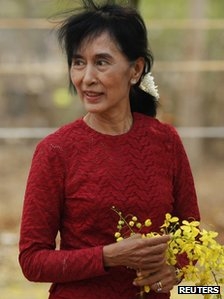 Aung San Suu Kyi carries flowers as she visits a polling station in Kawhmu township, Burma, 1 April 2012