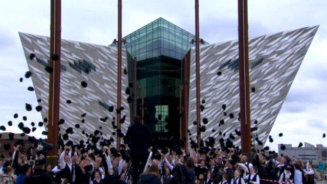 People in shipyard fancy dress in front of Belfast's new Titanic attraction