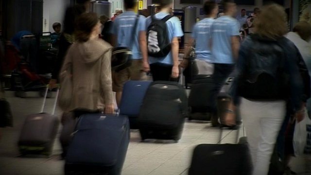 Air passengers carrying luggage in an airport