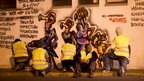 A photo taken at night with artists working behind Boniface Mwangi